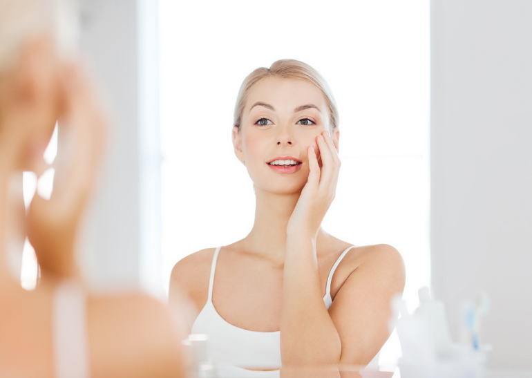 woman looking in the mirror, one hand on face admiring her healthy skin