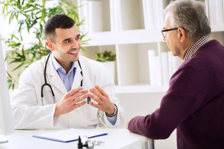 young male doctor smiling and speaking to an older male patient in a doctors office.