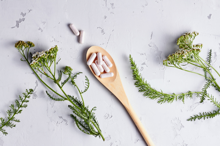medicine capsules on a wooden spoon, surrounded by 3 springs of greenery