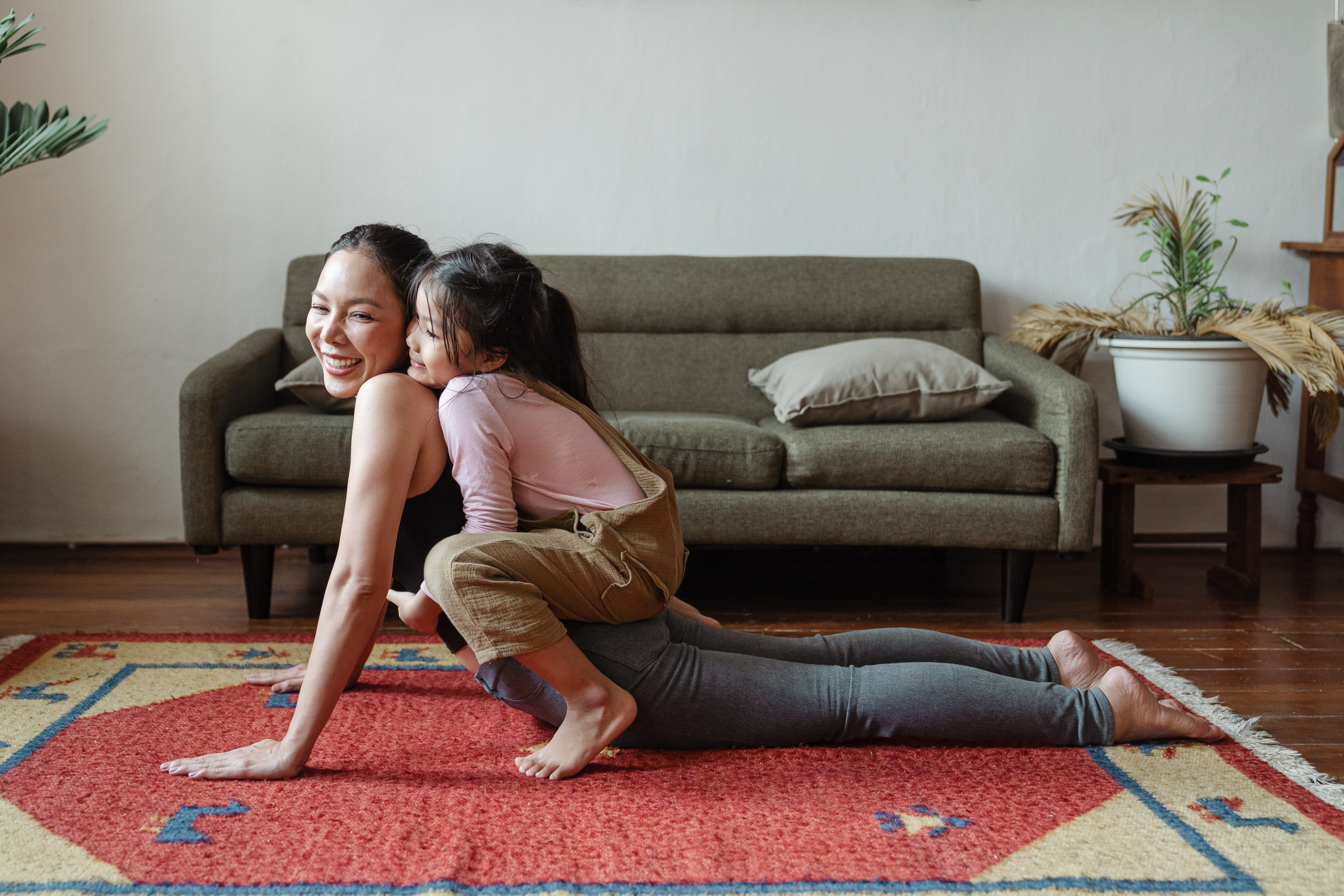 mom practicing yoga, smiling over her shoulder at daughter who is sitting on her back, hugging her from behind