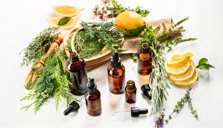 essential oils in dropper jars surrounded by sliced lemons and fresh and ground herbs